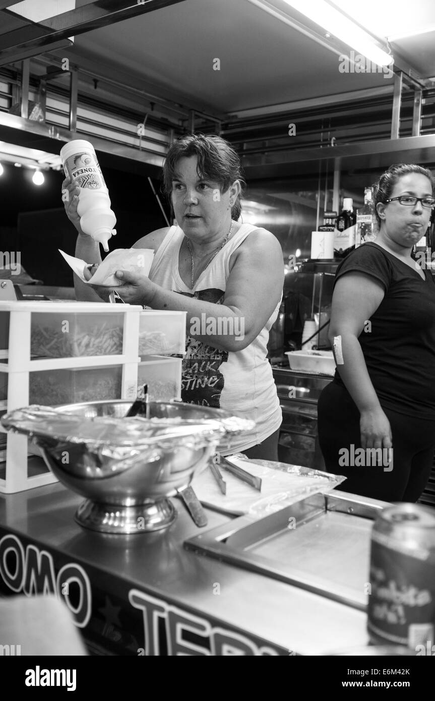 A woman pours mayonnaise on a hot dog serving from a fast food trailer at the San Juan annual fiesta, Tenerife, - Stock Image