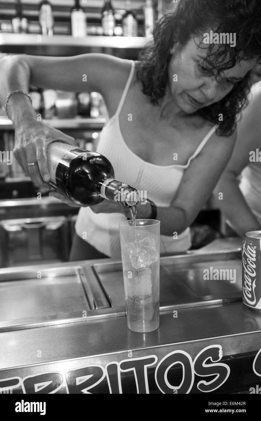 A woman pours rum over ice into a plastic tumbler at a fast food trailer at the San Juan annual fiesta, Tenerife, - Stock Image