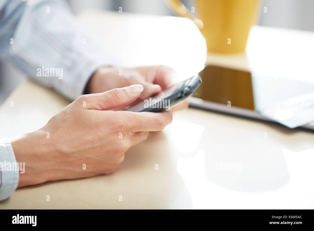 Hands of woman sending SMS via smartphone at lunch Stock