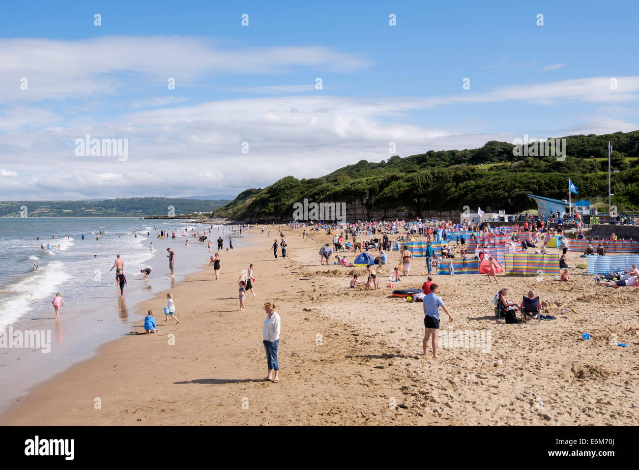 Holidaymakers and day-trippers on busy safe blue flag sandy beach in summer. Benllech, Isle of Anglesey, Wales, - Stock Image