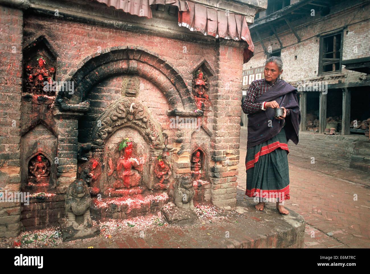 Newar woman worshiping a hindu deity ( Nepal) - Stock Image