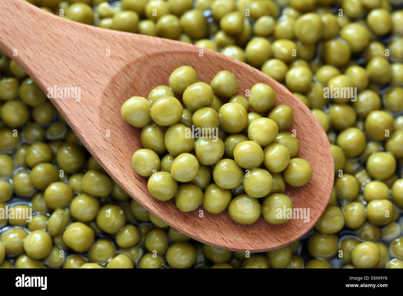 Preserved green peas in a wooden spoon on preserved green peas background. - Stock Image