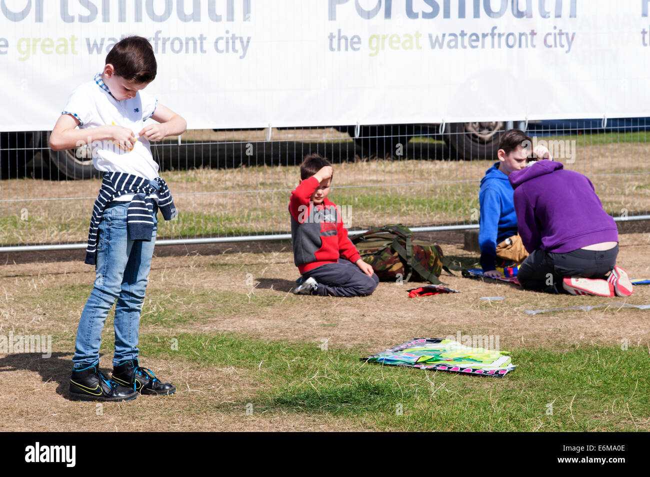 young boy prepares a kite as his mother helps his siblings next to the victorious festival 2014 southsea england Stock Photo