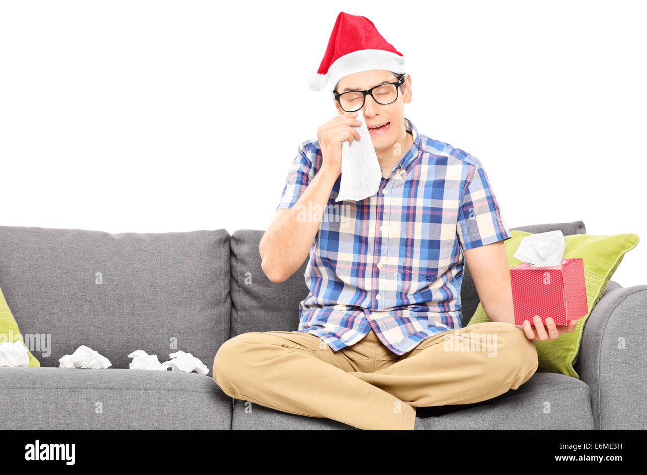 Sad man with Santa hat wiping his eyes from crying isolated on white - Stock Image