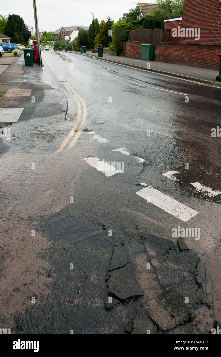 Water Leaking from a burst water main in the road - Stock Image