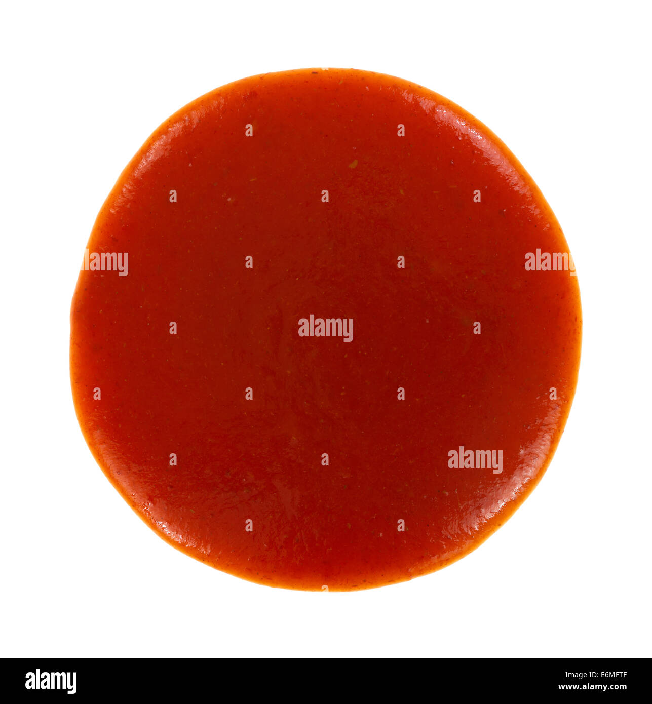 Top view of a round blob of red taco sauce on a white background. - Stock Image