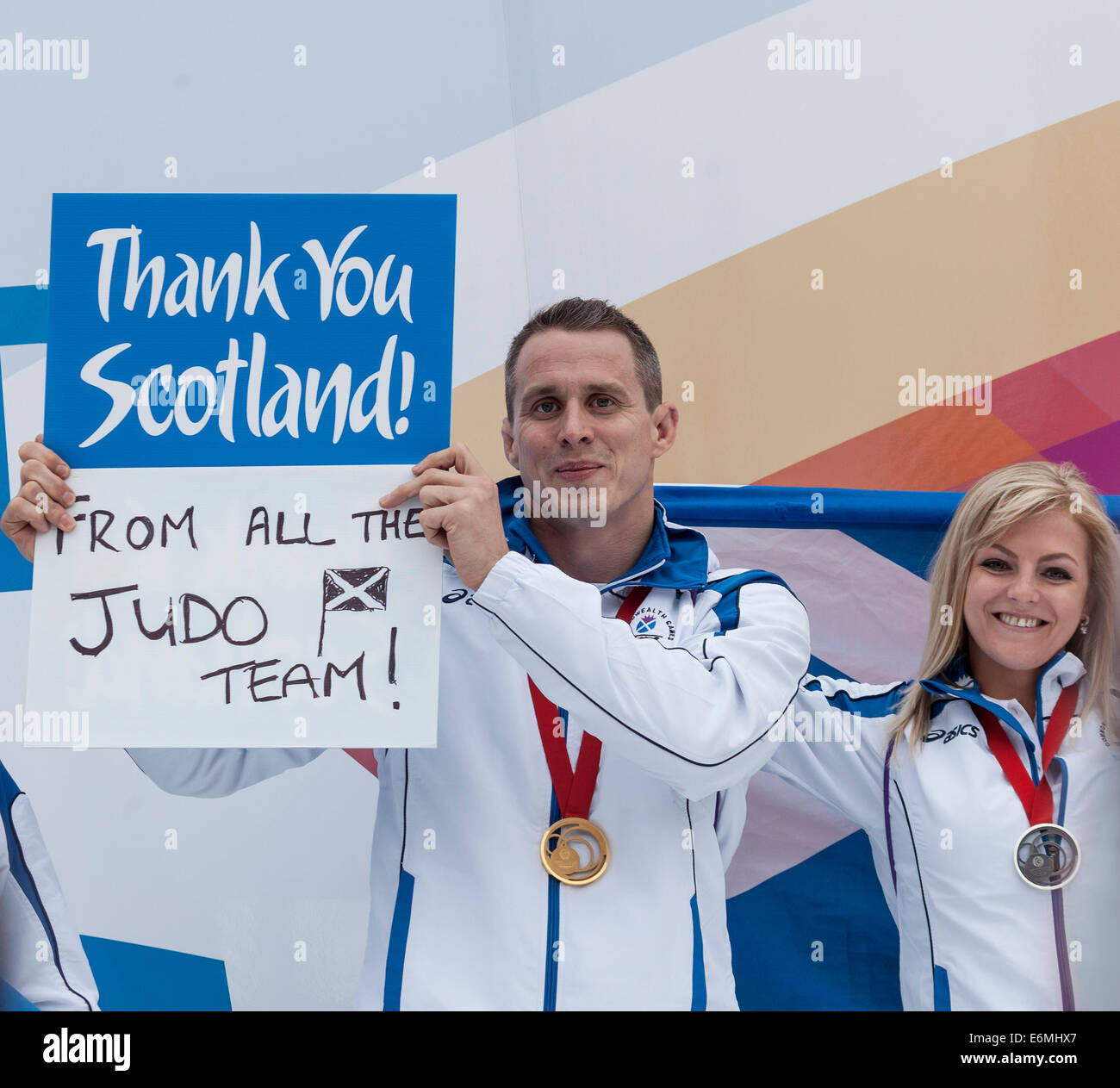 Euan Burton, gold medal judoka, holding up a Thank You Scotland sign, with silver medallist Stephanie Inglis, George - Stock Image