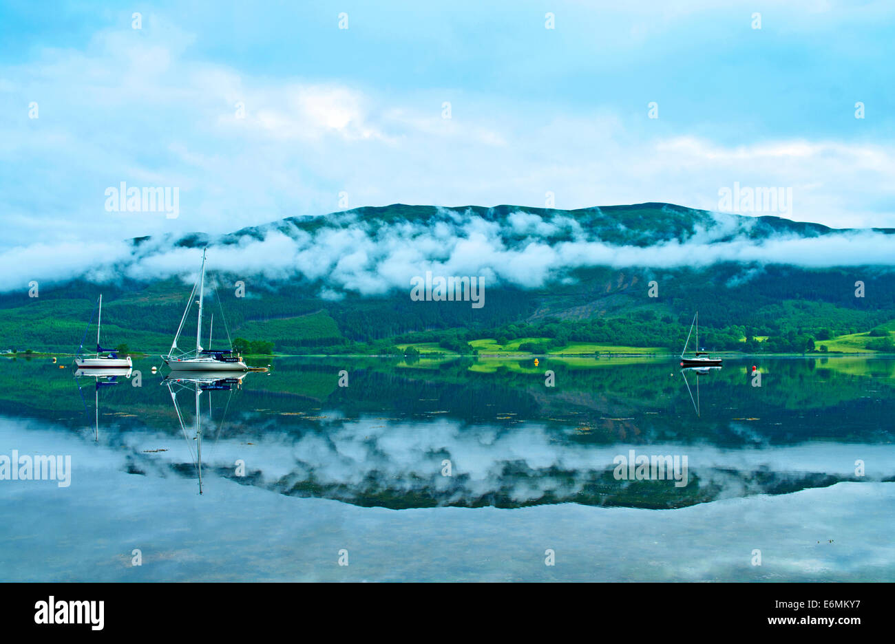 Early morning mist clings to hillside near North Ballachulish, seen across Loch Leven from Glencoe, Lochaber, Highlands - Stock Image