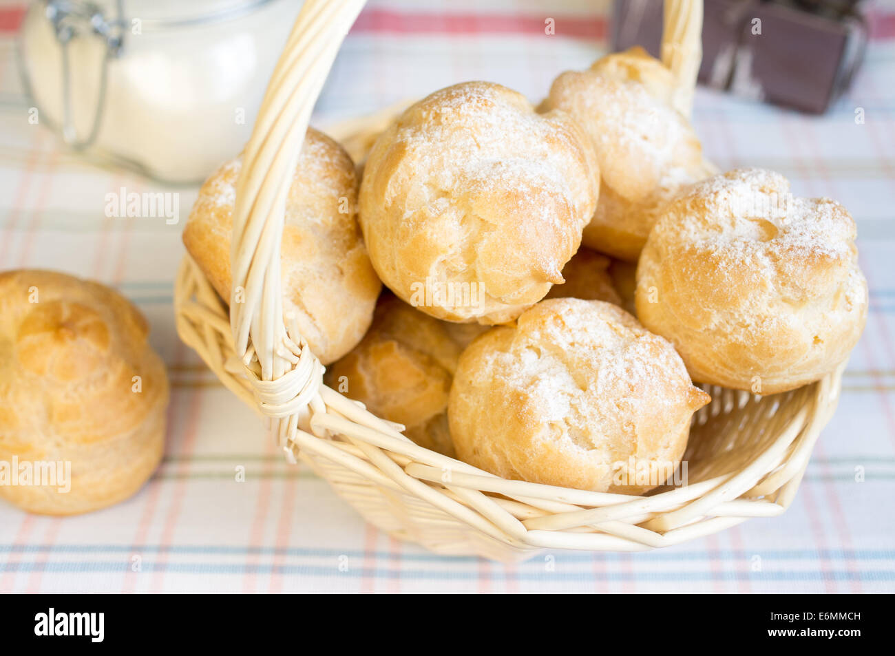 Cakes profiterole with cream in a basket - Stock Image
