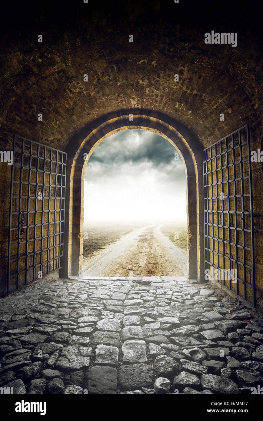 Old Arch Gate opening to Endless Country Road leading nowhere. Hopelessness and great unknown concept. - Stock Image