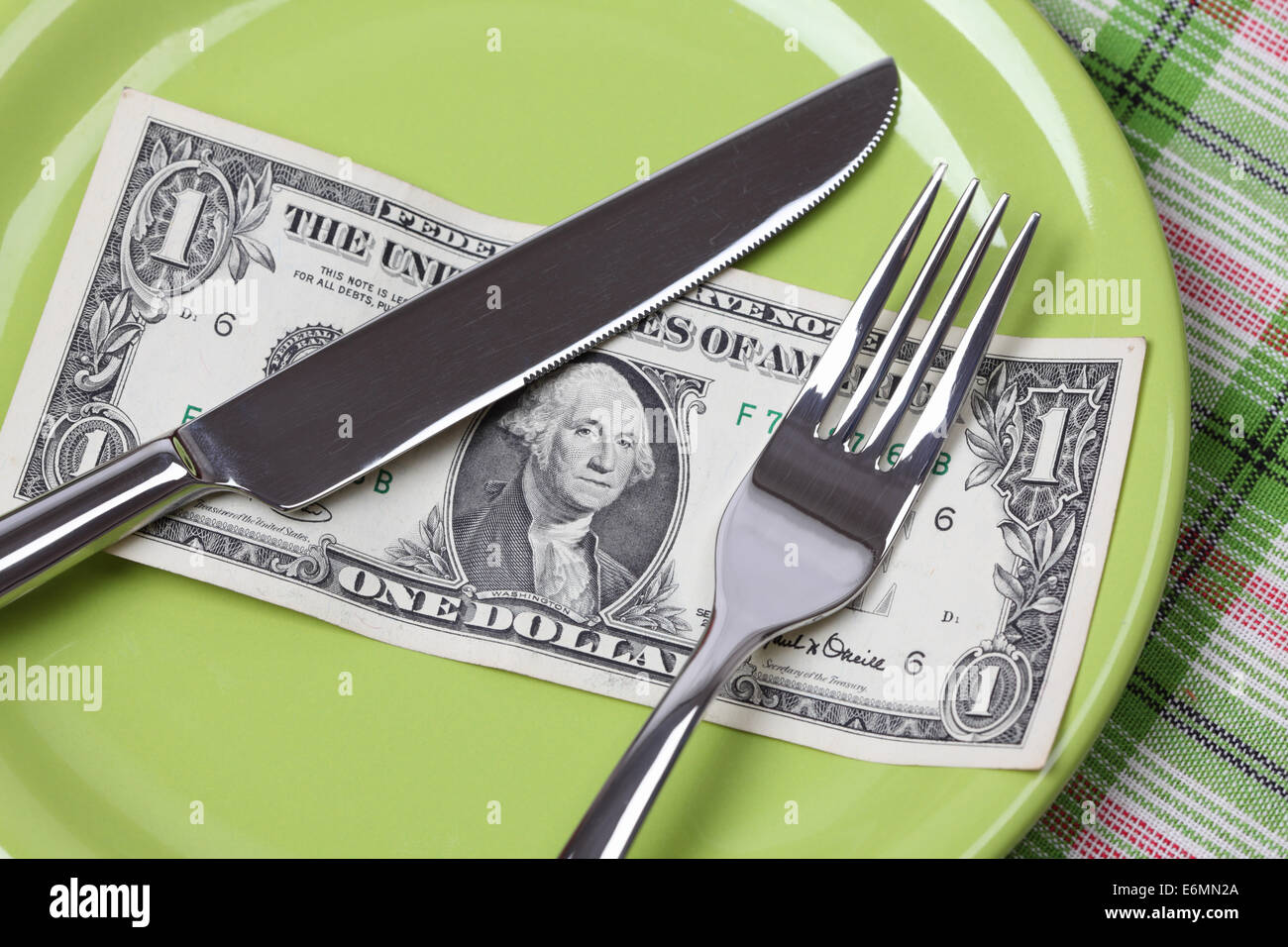 One Dollar Diet. One dollar on a plate with a knife and fork. Stock Photo