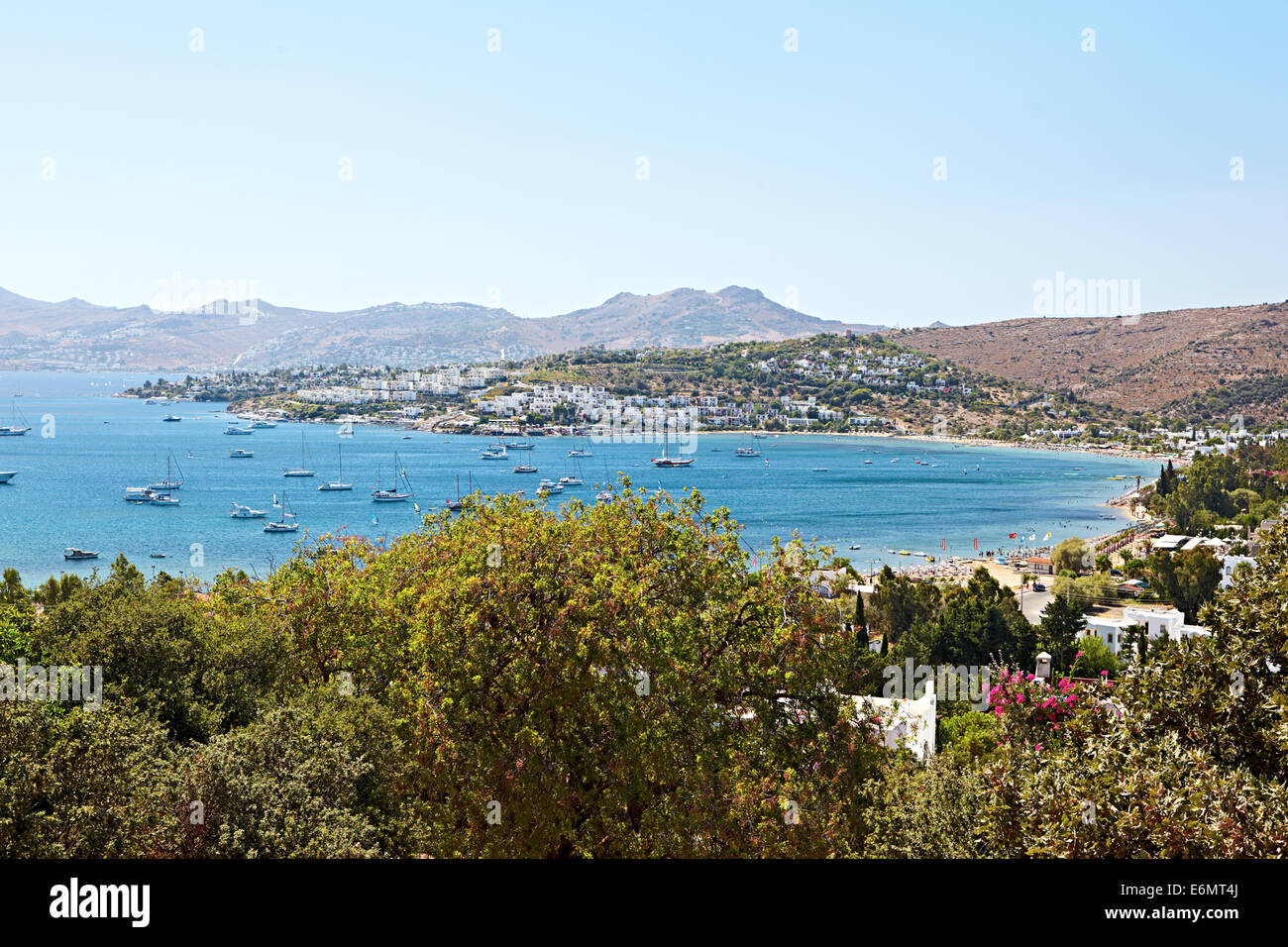 View over the bay looking out onto the boats and clear blue sea of Beyaz Beach Club, Bitez, Bodrum, Turkey - Stock Image