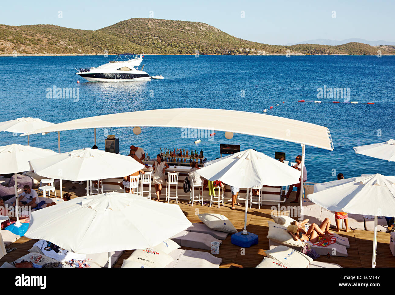 Holiday makers relaxing by the clear blue sea, watching boats go by and enjoying drinks at Beyaz Beach Club, Bitez - Stock Image