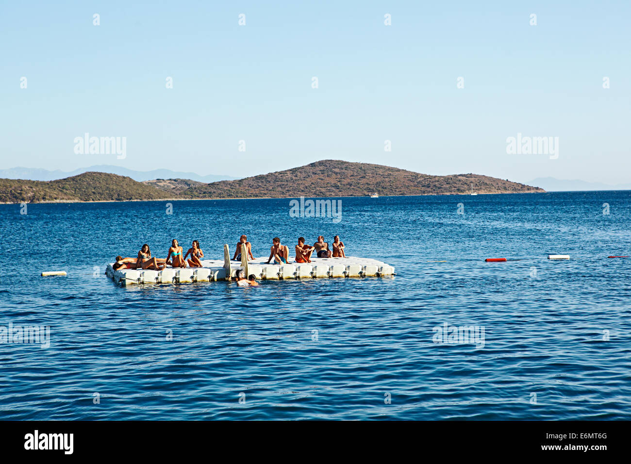 Holiday makers drifting on a raft in the clear blue see off Beyaz Beach Club, Bitez, Bodrum, Turkey - Stock Image