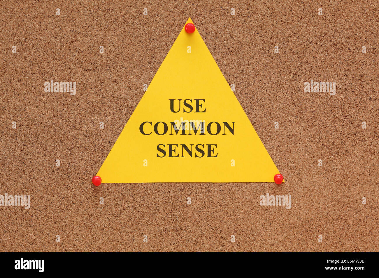 Triangular paper note with the words 'use common sense' on cork board (bulletin board). - Stock Image