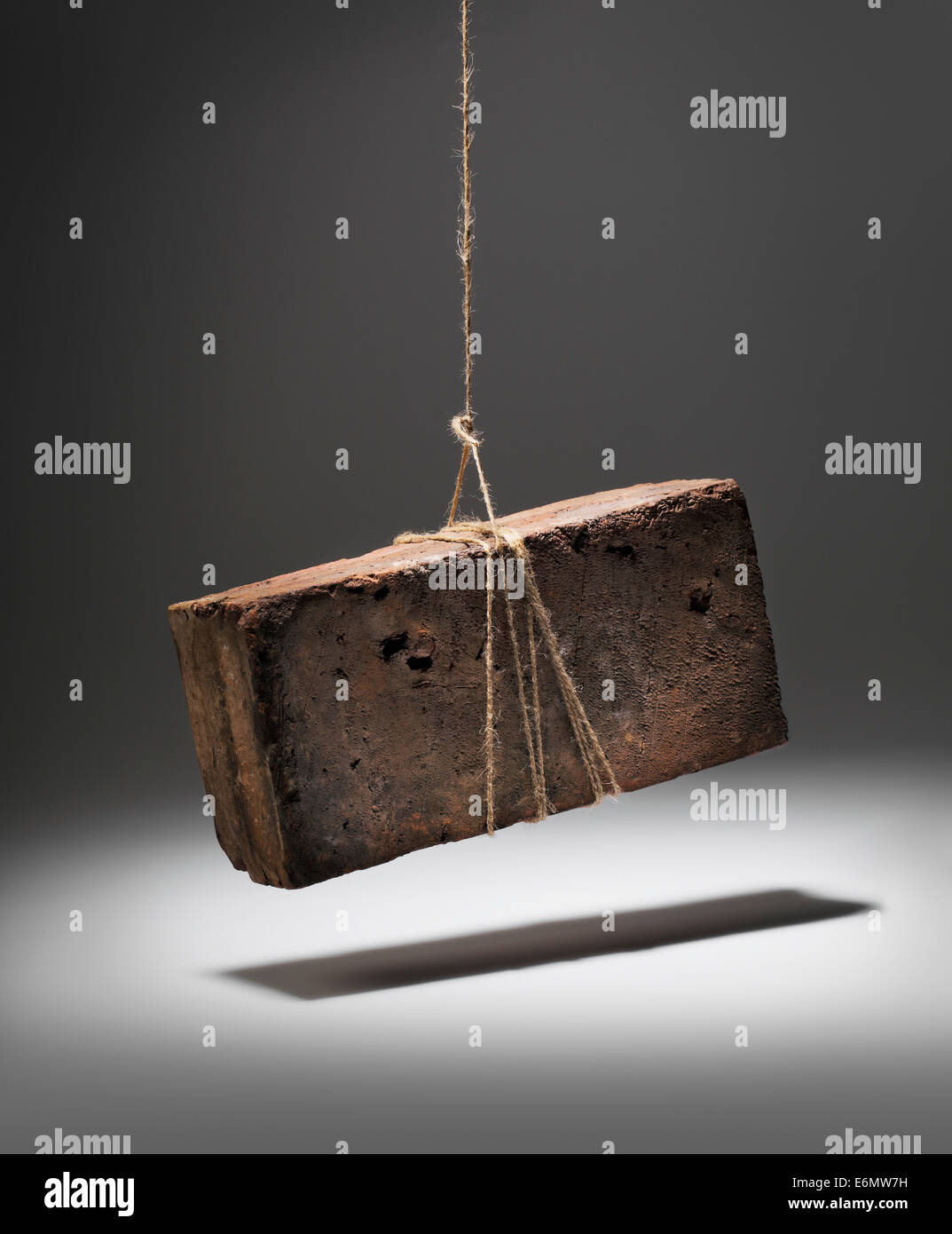 Old worn and weathered brick hanging on a string. - Stock Image