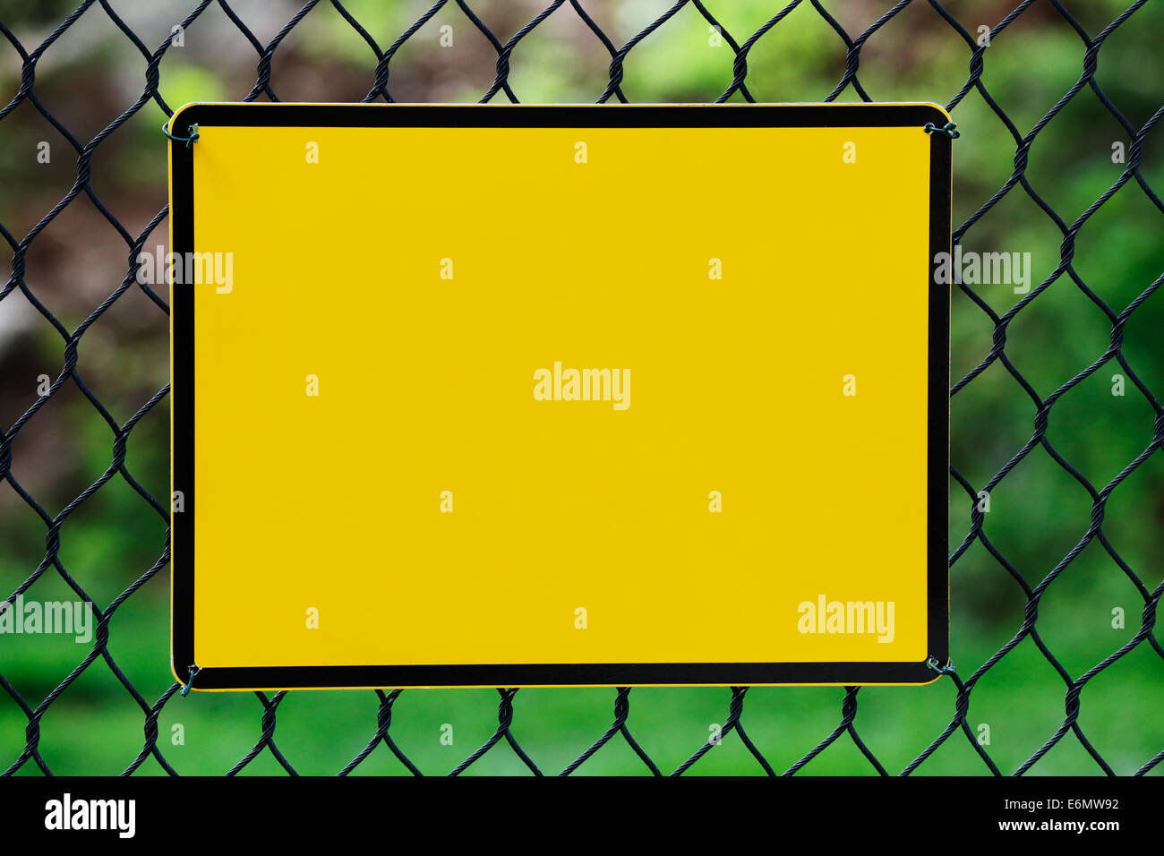 Blank yellow info plate hung on a wire fence - Stock Image