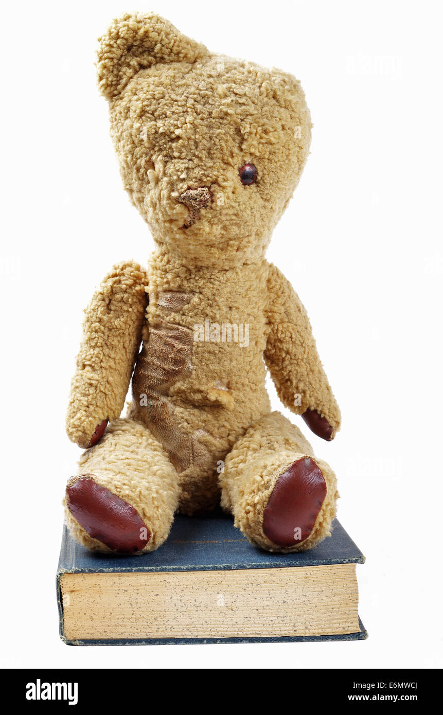 old worn teddy bear sitting on a old blue book - Stock Image