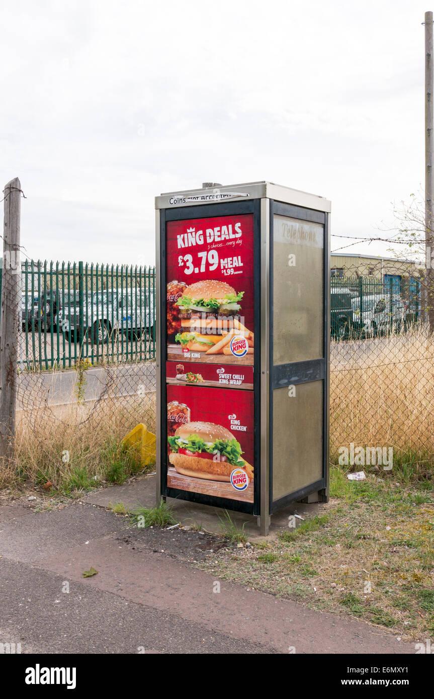 Burger King food advertising posters on UK public telephone kiosk - Stock Image