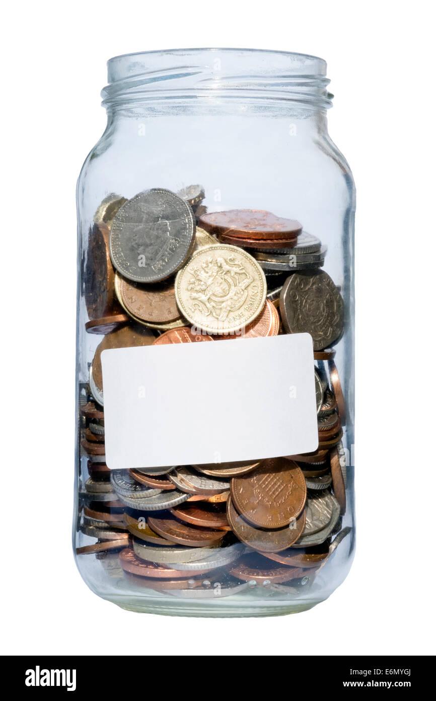 Jam jar full of coins, UK. Glass jar containing pounds & pennies savings. - Stock Image