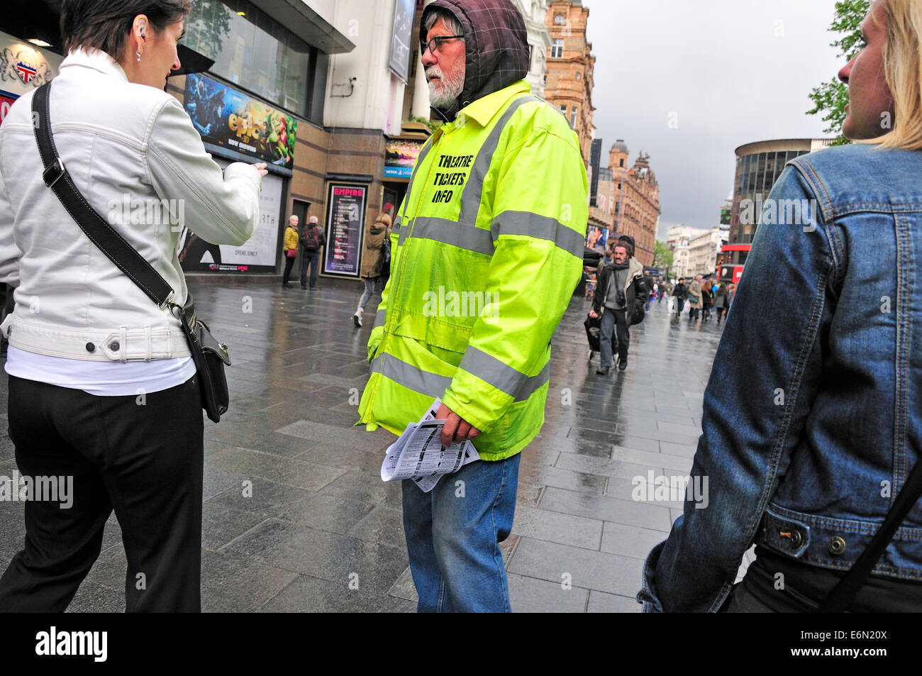 London, England, UK. Man with Theatre Information in Leicester Square in the rain - Stock Image
