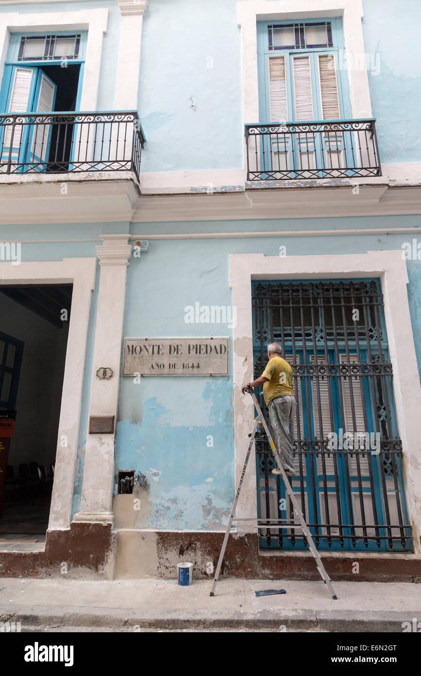 man painting facade, Monte de Piedad coin museum, old Havana, Cuba - Stock Image