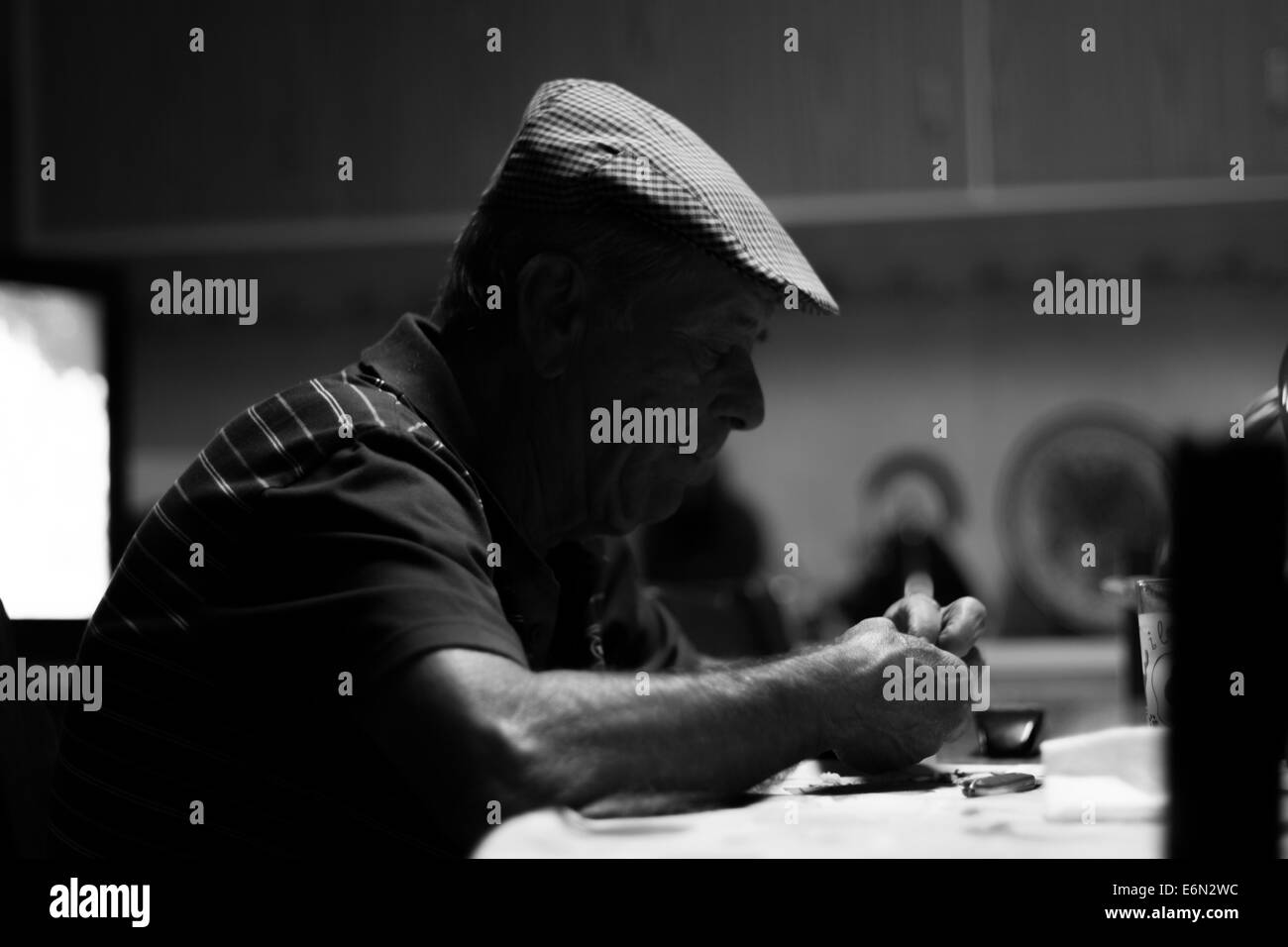 old man sitting at table - Stock Image