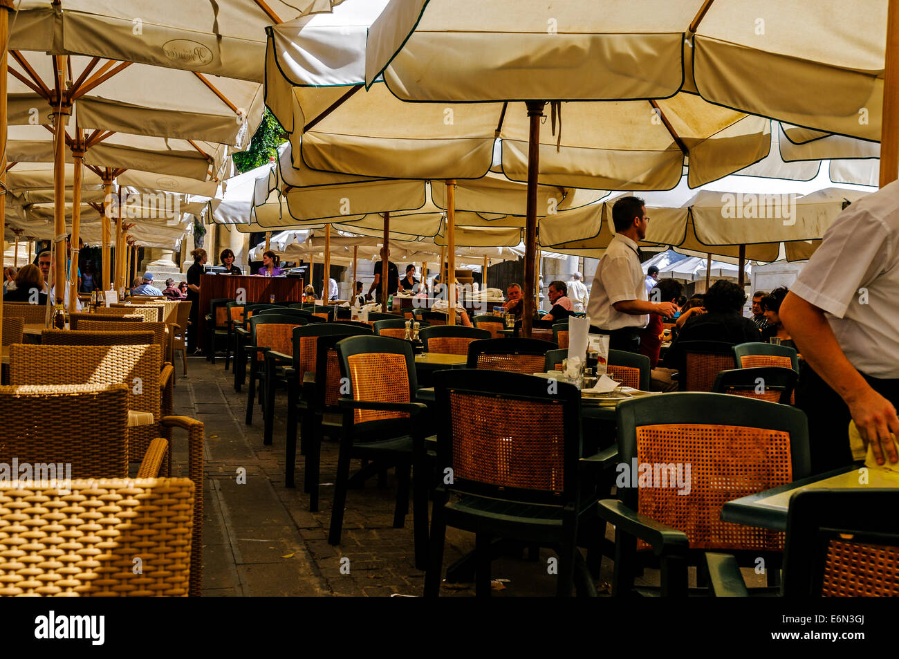 Diners using a typical restaurant on the harbour front providing food and drink in comfortable shady surroundings, - Stock Image