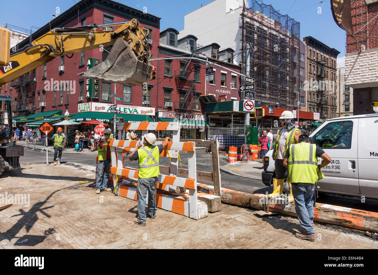 Construction workers guiding the shovel of a backhoe loader on Mulberry Street in New York City - Stock Image