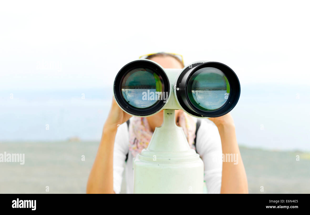 Woman looking through binoculars or telescope - Stock Image