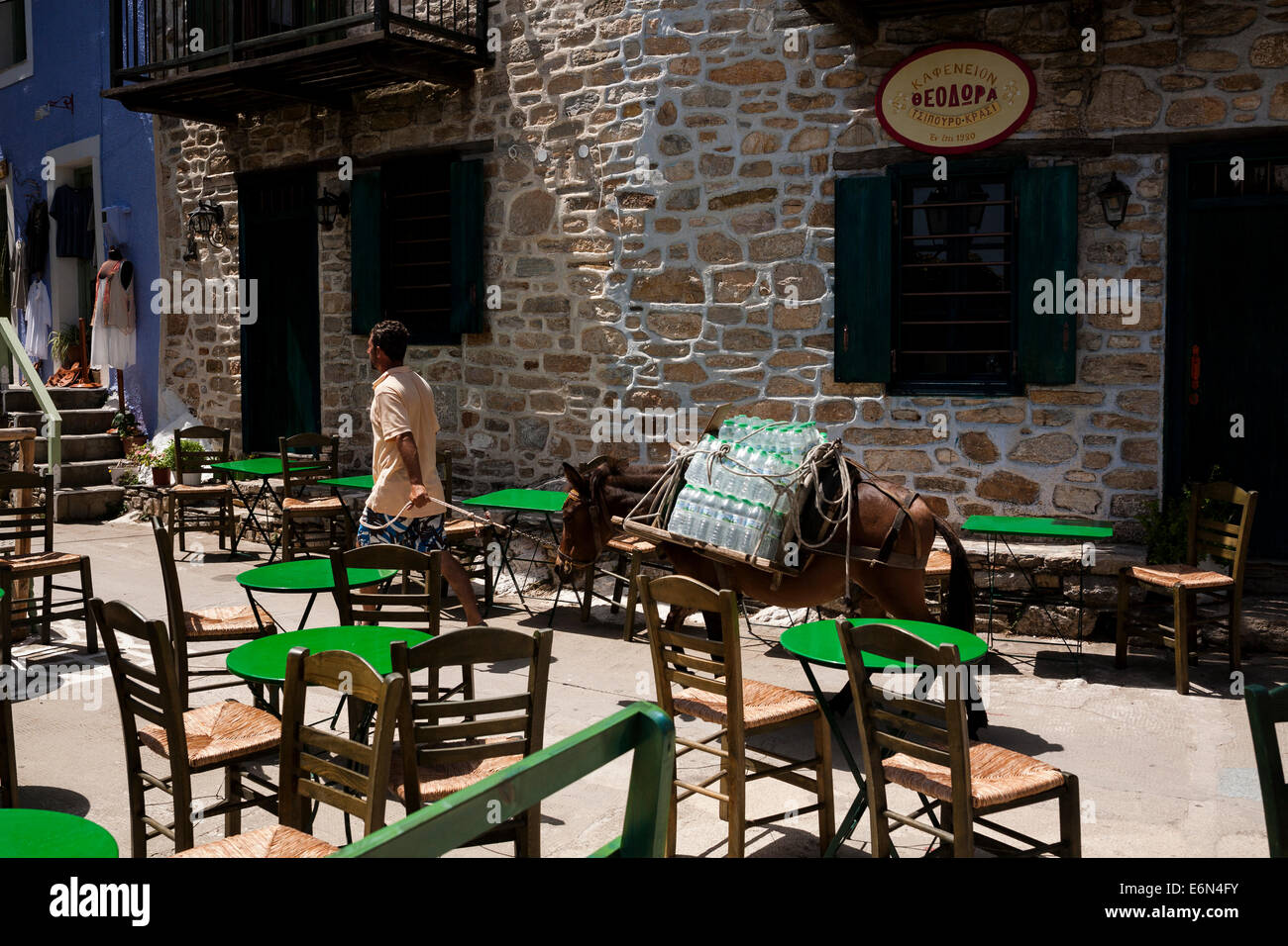 A man uses a mule to carry bottled waters at the Old Village of Alonnisos, Greece on August 2014. - Stock Image