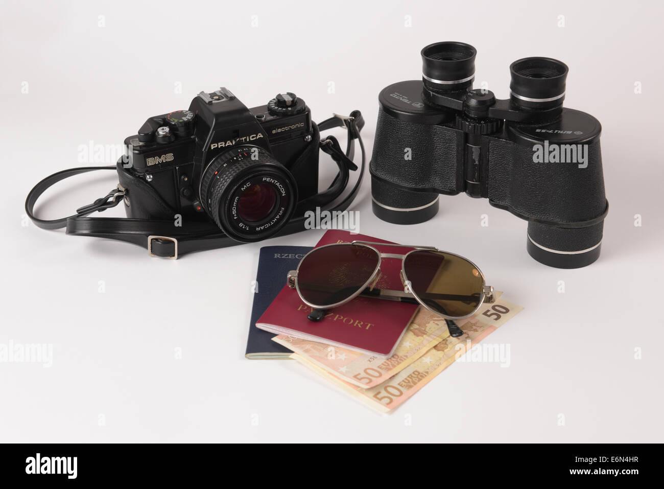 Old analog camera, binocular, sunglasses and passports with some money. Stock Photo
