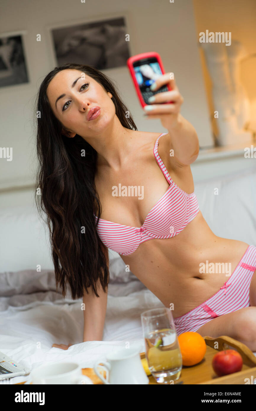 899f38713179 A pretty young woman girl wearing pink underwear taking a sexy selfie photo  on her mobile phone in bedroom UK