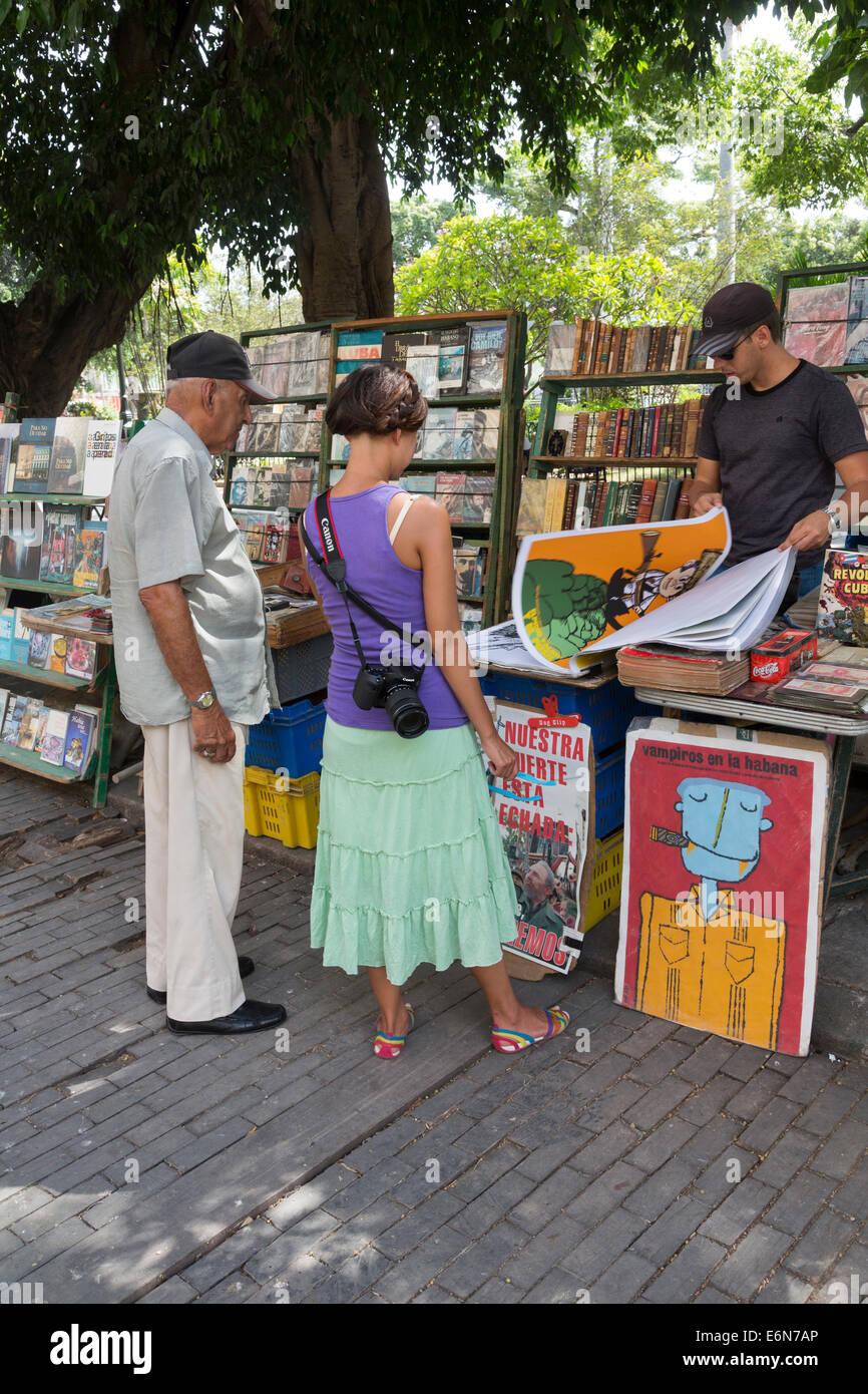tourist looking at posters for sale, Plaza de Armas, old Havana, Cuba - Stock Image
