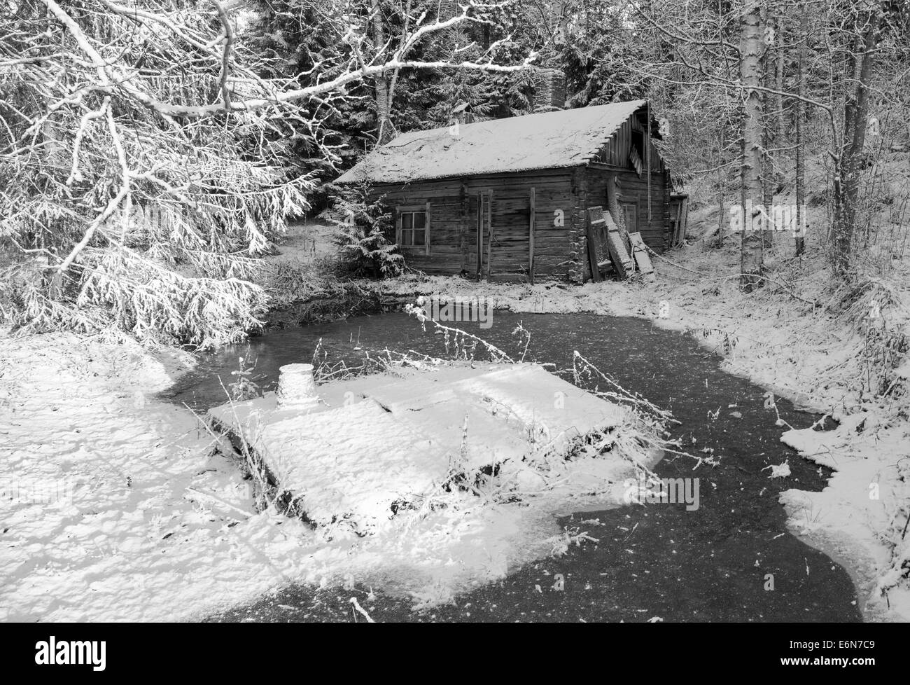 Old decaying wooden sauna building and a well at Winter at Finnish countryside , Finland - Stock Image