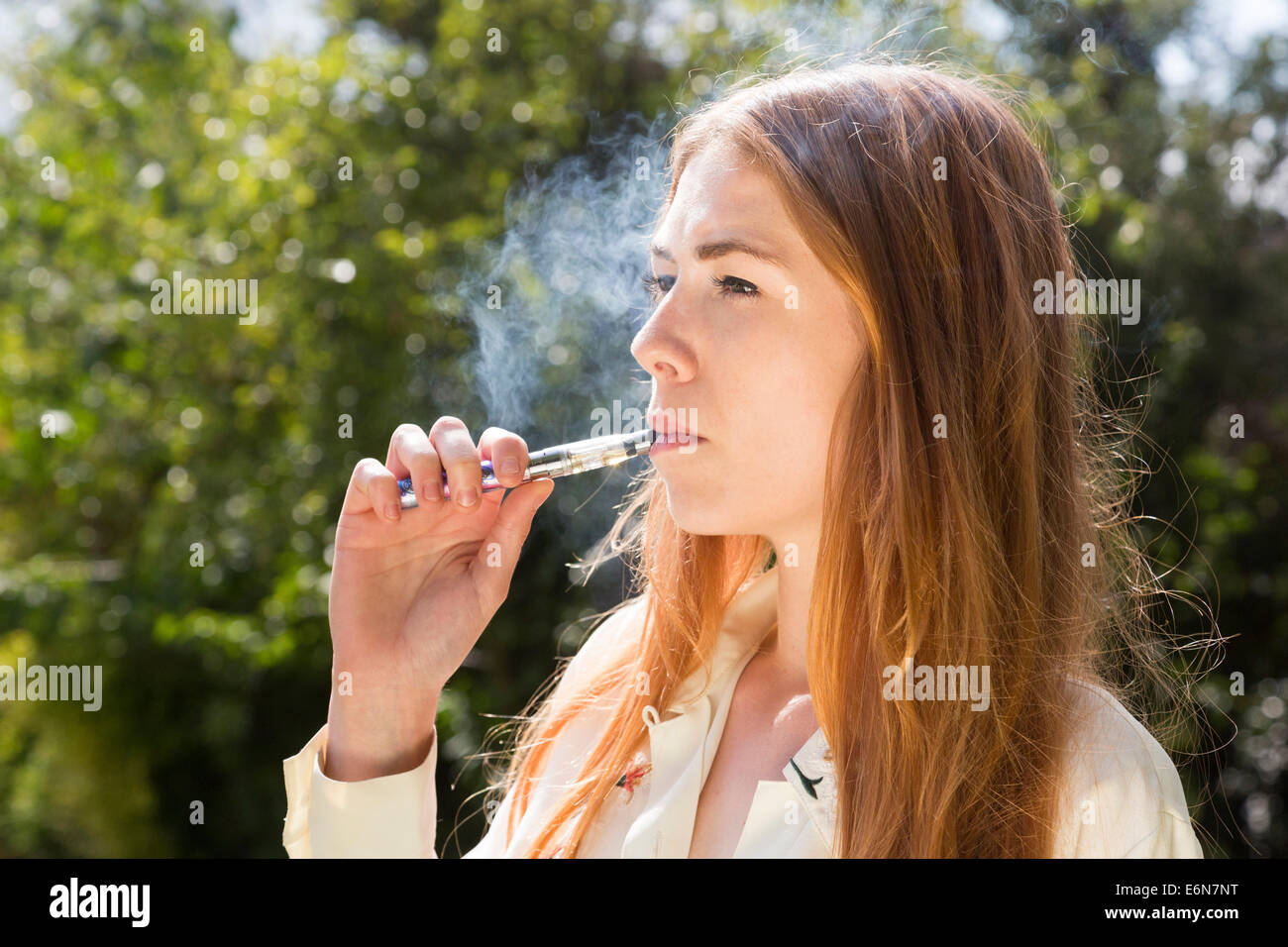 young woman smoking an electronic e-cigarette - Stock Image