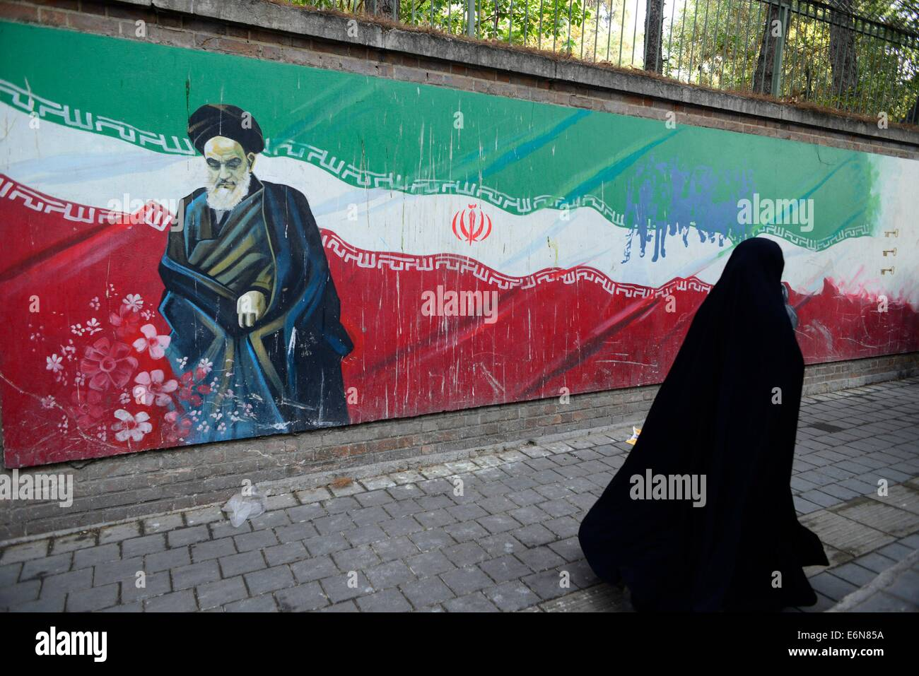 veiled Iranian woman, walks past a Ayatollah Khomeini's picture painted on a wall of the former US Embassy in - Stock Image