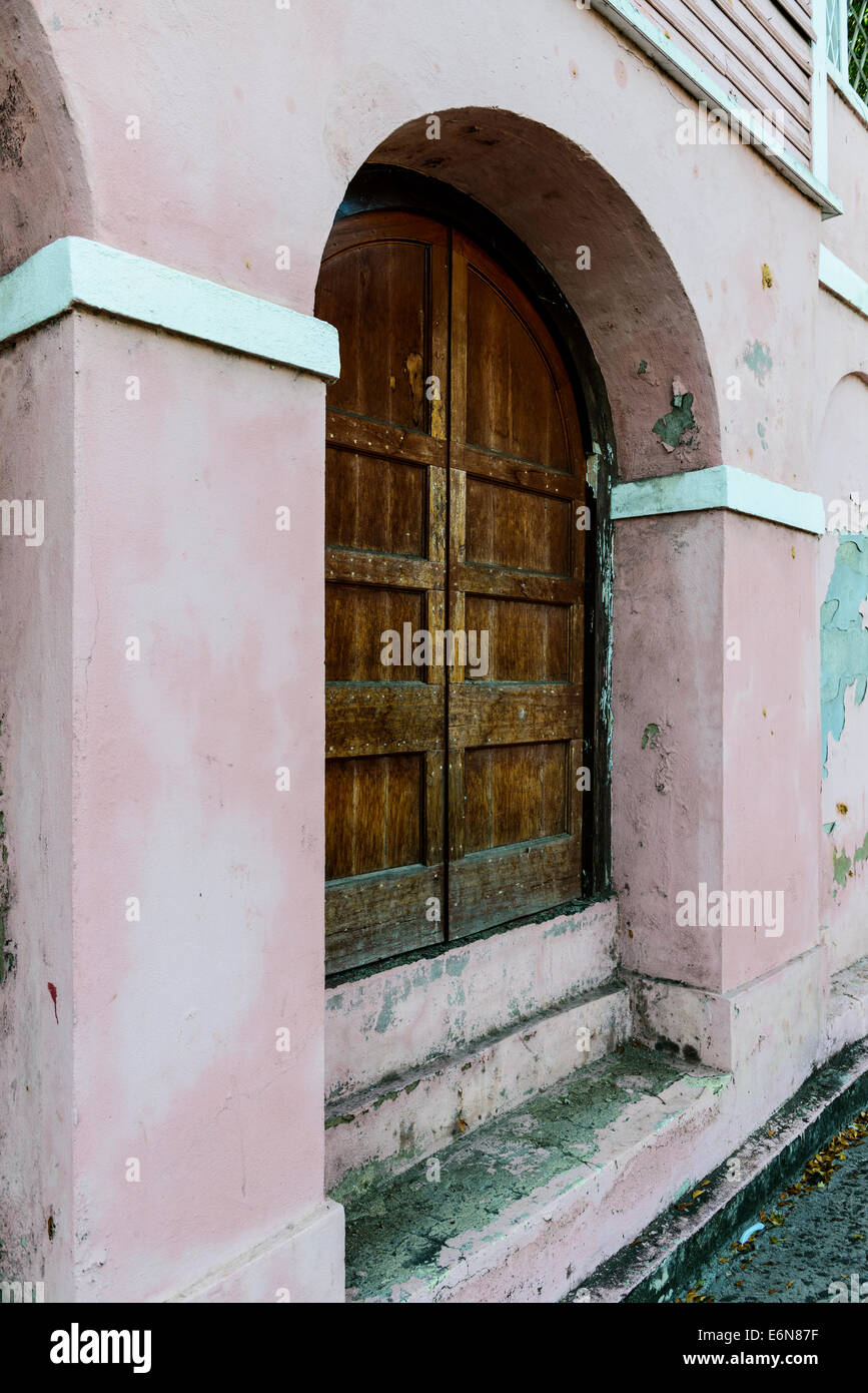 A Paneled Old Wooden Set Of Exterior Doors Under An Arched Entry Of
