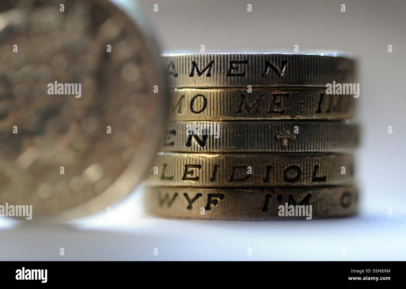 BRITISH ONE POUND COINS WITH EDGE LETTERS SPELLING 'MONEY' RE WAGES INCOMES MORTGAGES CURRENCY HOUSEHOLD - Stock Image
