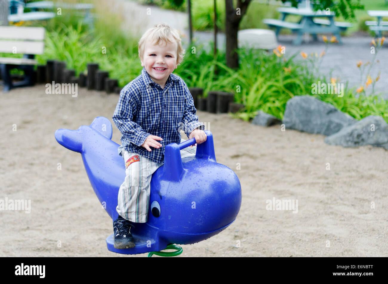 A smiling happy young boy playing in a playground - Stock Image