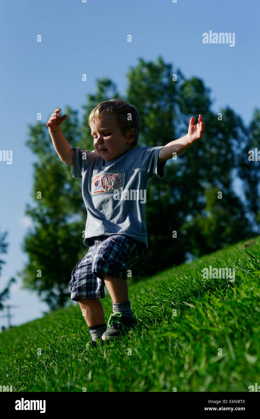 A young boy running down a grassy slope - Stock Image