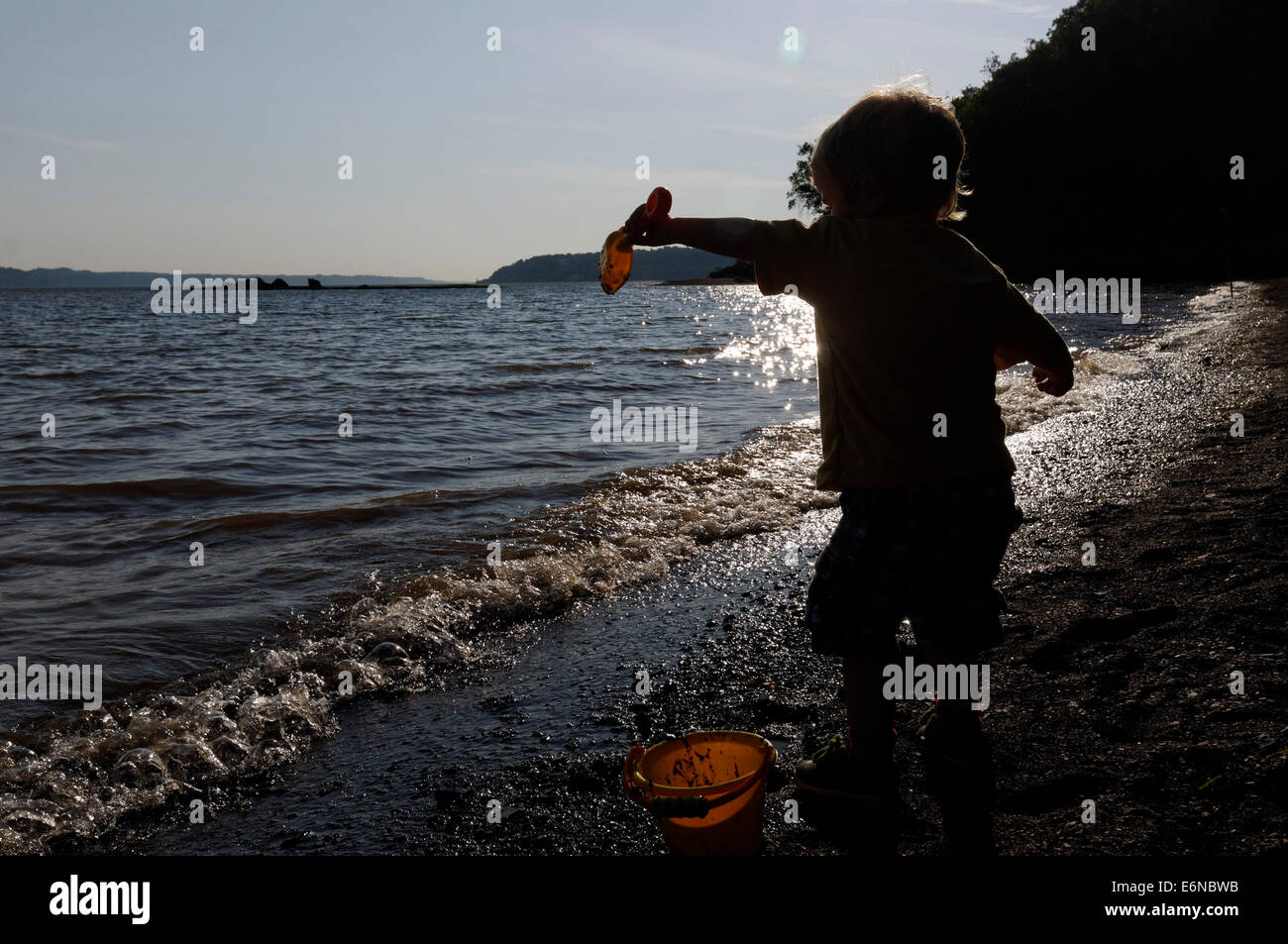 A young boy playing with a bucket and spade on the beach, Plage Jacques Cartier, Quebec on the St Lawrence shoreline - Stock Image