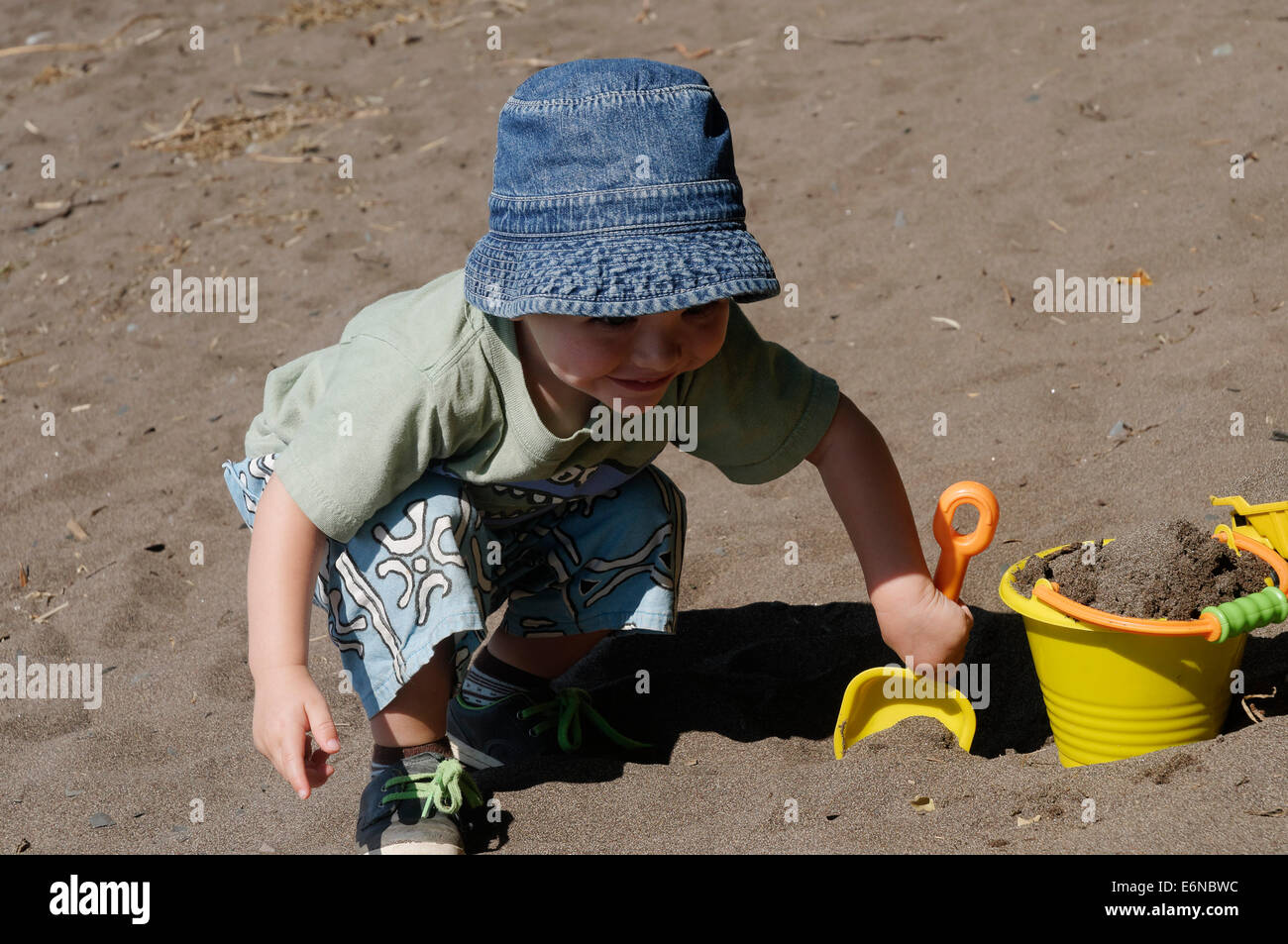 A young boy playing with a bucket and spade in the sand - Stock Image