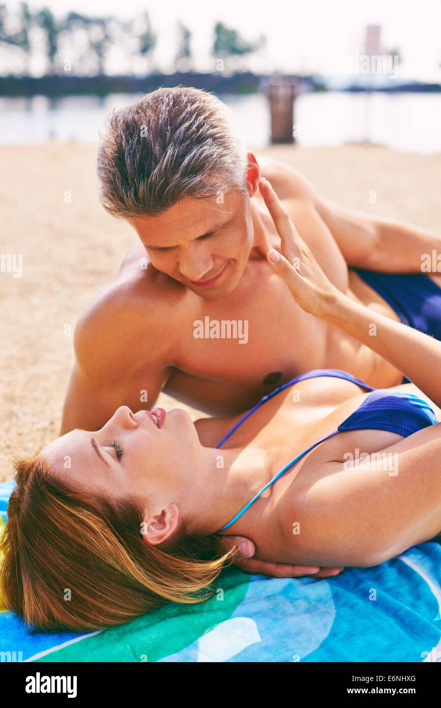 Woman and man relaxing on beach Stock Photo