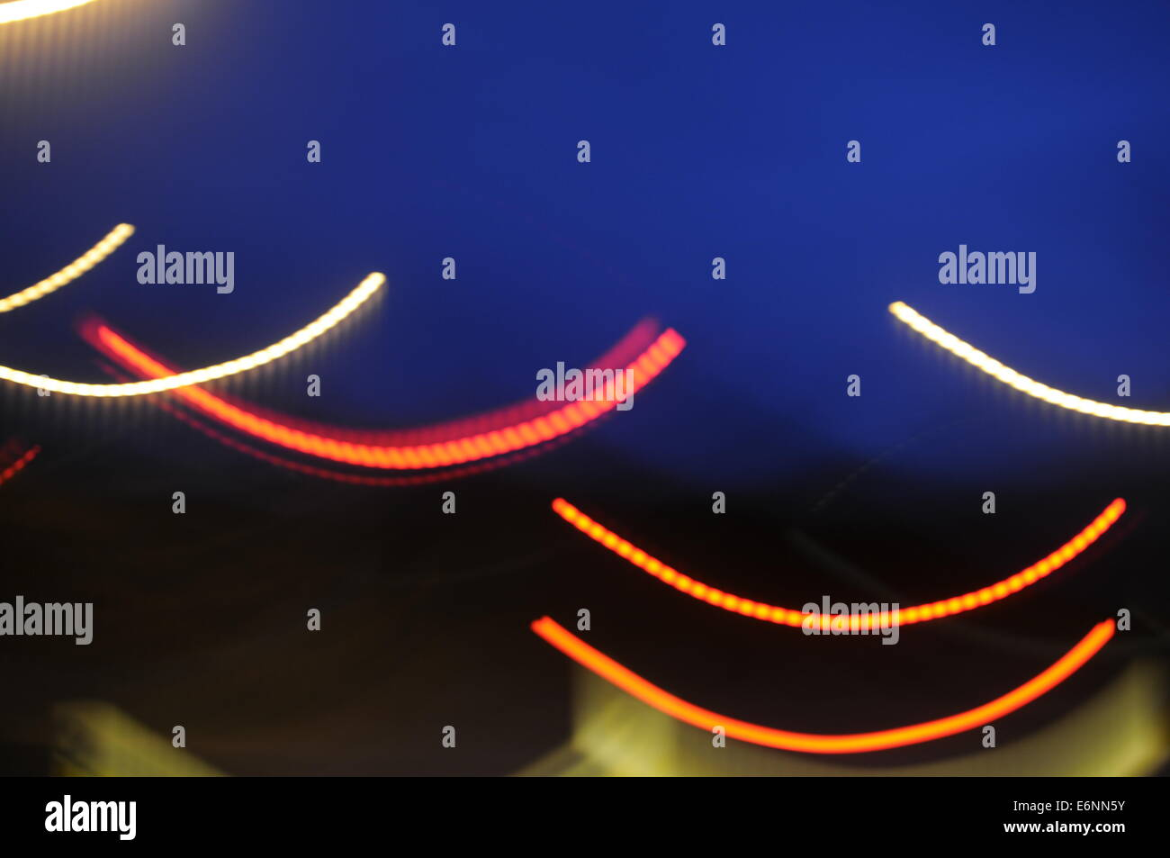 different coloured curved light trails - Stock Image