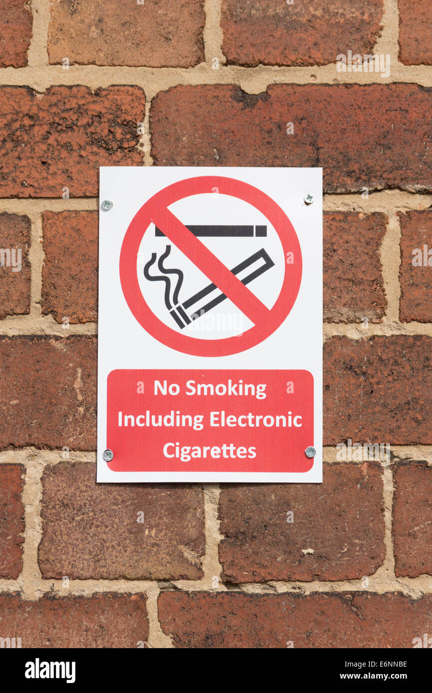 No smoking sign, including no smoking electronic cigarettes, fastened to a brick wall. - Stock Image