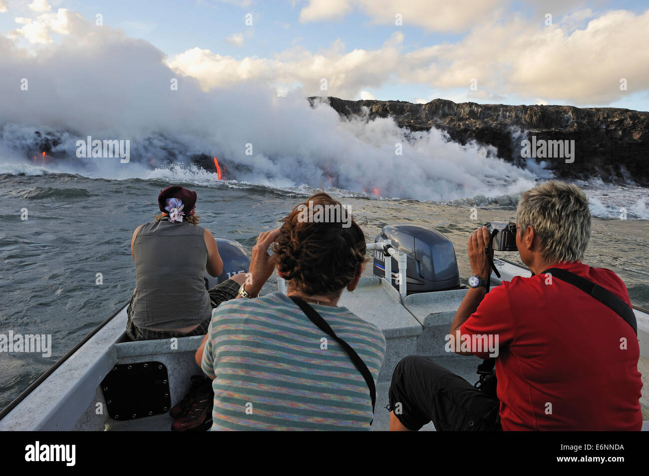 People photographing lava flowing to the sea from a boat, Kilauea Volcano, Big Island, Hawaii Volcanoes National - Stock Image