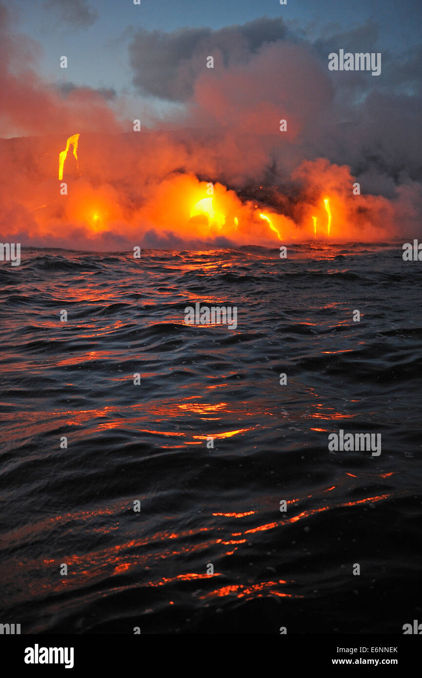 Steam rising off lava flowing into ocean at dusk, Kilauea Volcano, Big Island, Volcanoes National Park Hawaii, USA - Stock Image