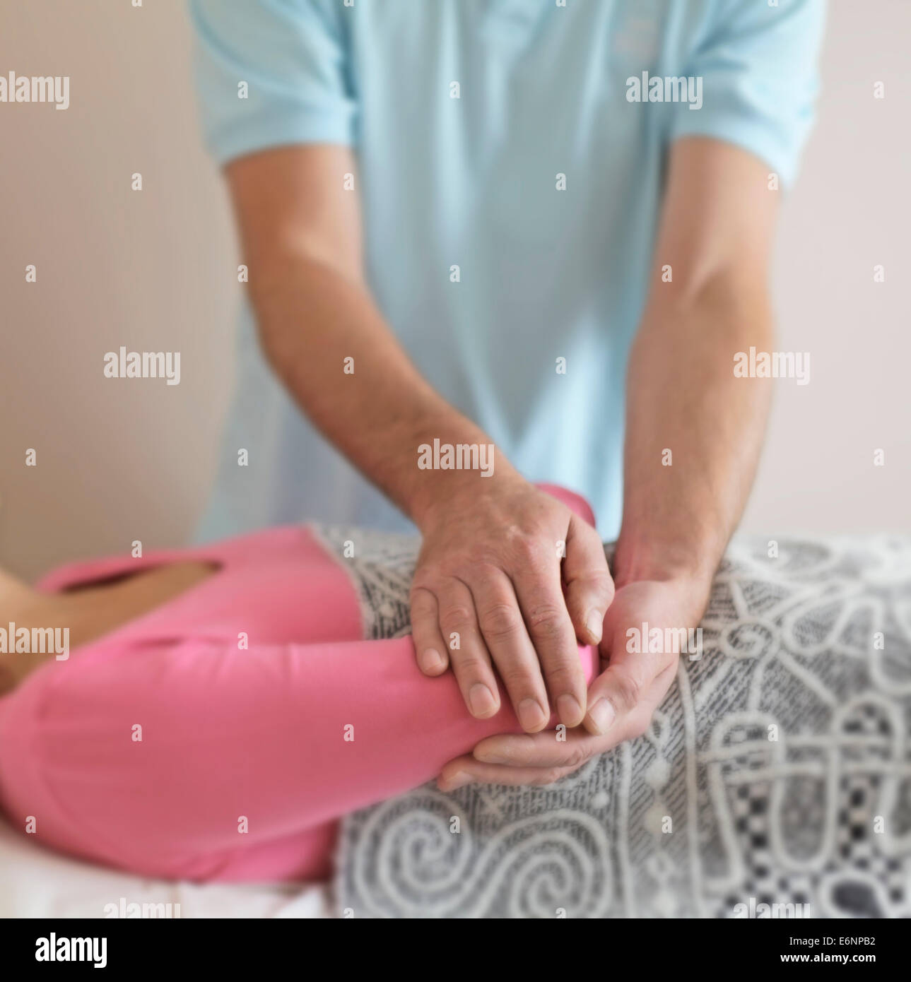 Male healer holding female patient's elbow gently channeling healing energy - Stock Image