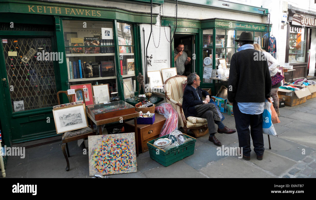 People talking relaxing outside Keith Fawkes antique shop on Flask Walk in Hampstead Village North London NW3 UK - Stock Image